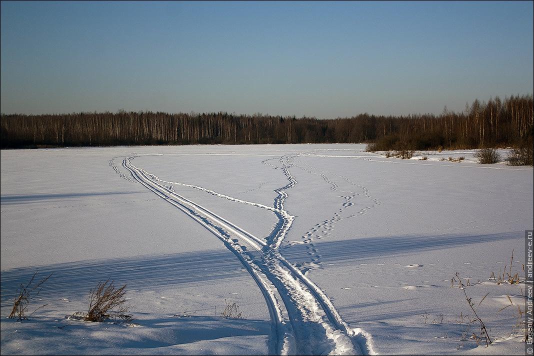 Следы снегохода на озере